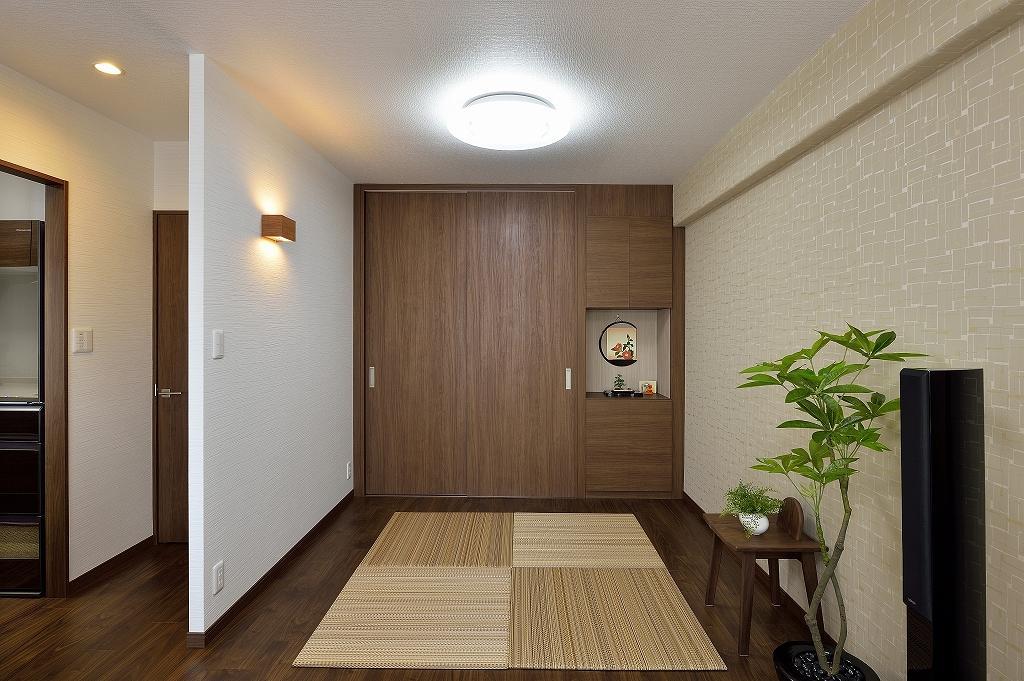 リビングの畳コーナー、壁一面はウォークインクローゼットと飾り棚を同じカラーでまとめてすっきりとした印象。
