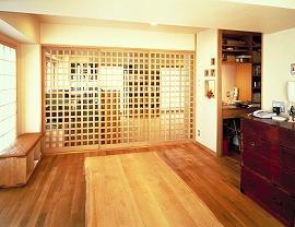 施主様は在宅でお仕事をされており、自然素材にこだわられたマンションのリビング。奥は、仕事場兼和室。間仕切りに格子戸を採用したことで、風通しがよく日当たりもよい。