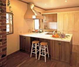 英国田舎風をイメージした家のキッチン。 オープンキッチンの天板は大ぶりの白タイル、収納部はブラウンの木目、壁の一部にはレンガが貼ってあり、英国田舎風の雰囲気をうまく出してる。