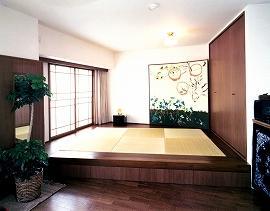 リビングにつくった床上げ和室は、リビングとの間を斜めに区切り、側面には大容量の収納スペースが。琉球畳のまわりはダークブランの板間。フローリングとも色を合わせ、重厚感のある空間に。
