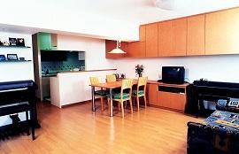 元は2つの和室のあったスペースに造ったリビングダイニング。壁面に大容量の吊戸棚と、収納ボード。フローリングや家具も収納棚に合わせナチュラルな木目調で、すっきりまとまっている。