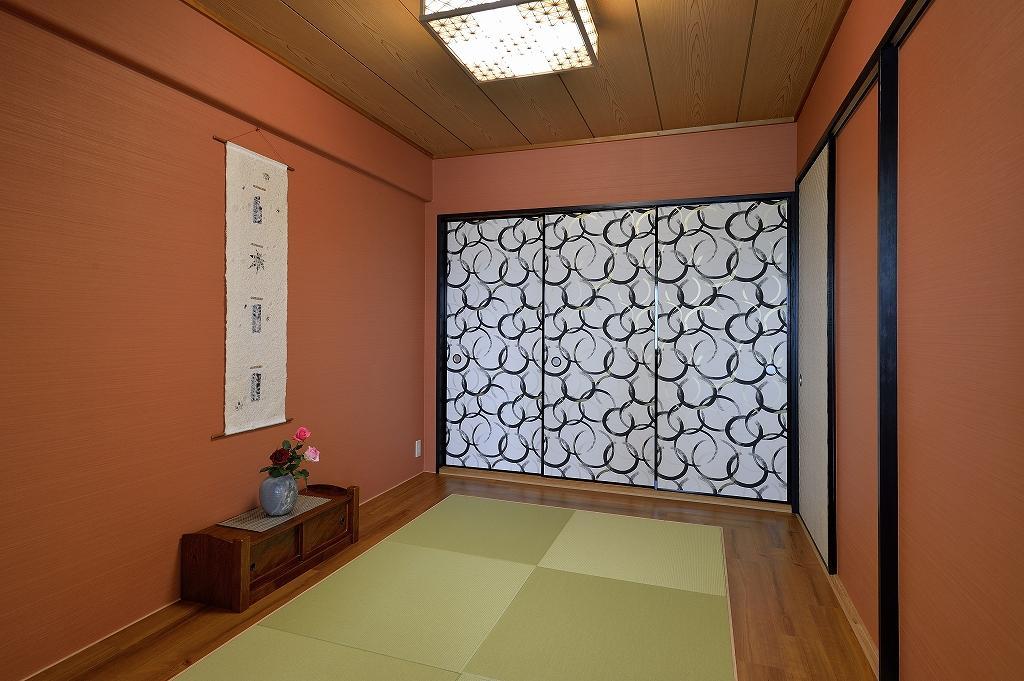 和モダン旅館のようなリビング横の和室。朱色のオシャレ壁紙と、粋なデザインの襖紙がアクセント。