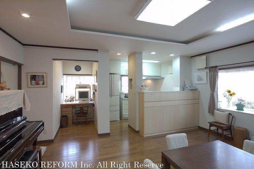 2列型の対面式キッチンのある、リビングダイニング。キッチンのリビング側カウンターが全面収納となっている。光を取り入れながら収納スペースも確保。