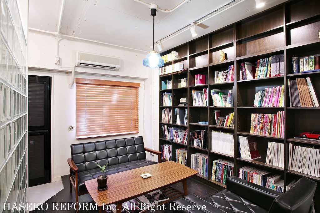 ガラスブロックのパーテーションで仕切られたSOHOのミーティングコーナー。天井まで連なる本棚とレトロデザインのソファが大人の隠れ家のような雰囲気をだしている。