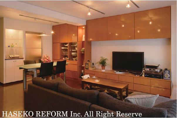 スペースをゆったりとったリビングは、優しい茶色の木目柄を基調にし、建具やキッチンにシルバーを取り入れ、アクセントに。大容量の壁面収納は、ご主人のコレクションを飾るスペースとして充実。