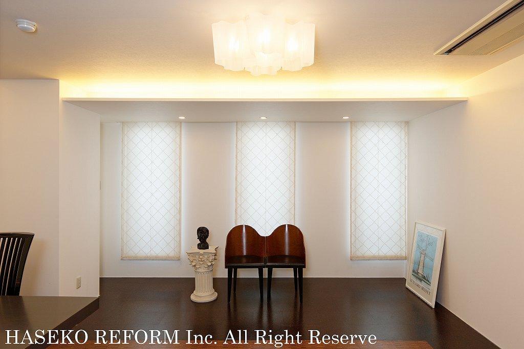 美術館のようなリビングの一角。さりげなく置かれた2脚の椅子と天井を柔らかく照らす間接照明が雰囲気をだしている。