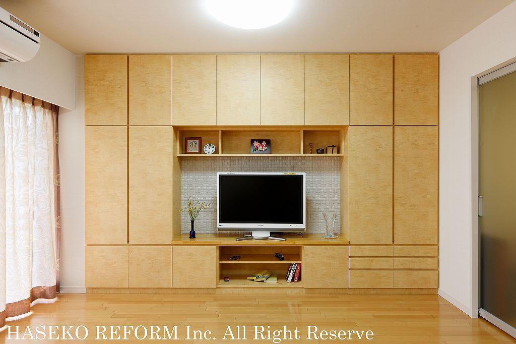 壁いっぱいに造り付けたリビングの壁面収納。テレビも設置でき、収納力抜群。フローリングの色に合わせ、ナチュラルな木目調にし、まとまりを感じる。