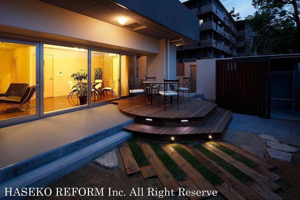 マンション1階の専用庭には、リビングからの段差を活かした円形のステージ風ウッドデッキを設置。足元のLED照明が芝生や枕木を照らし、昼間とは違った雰囲気に。