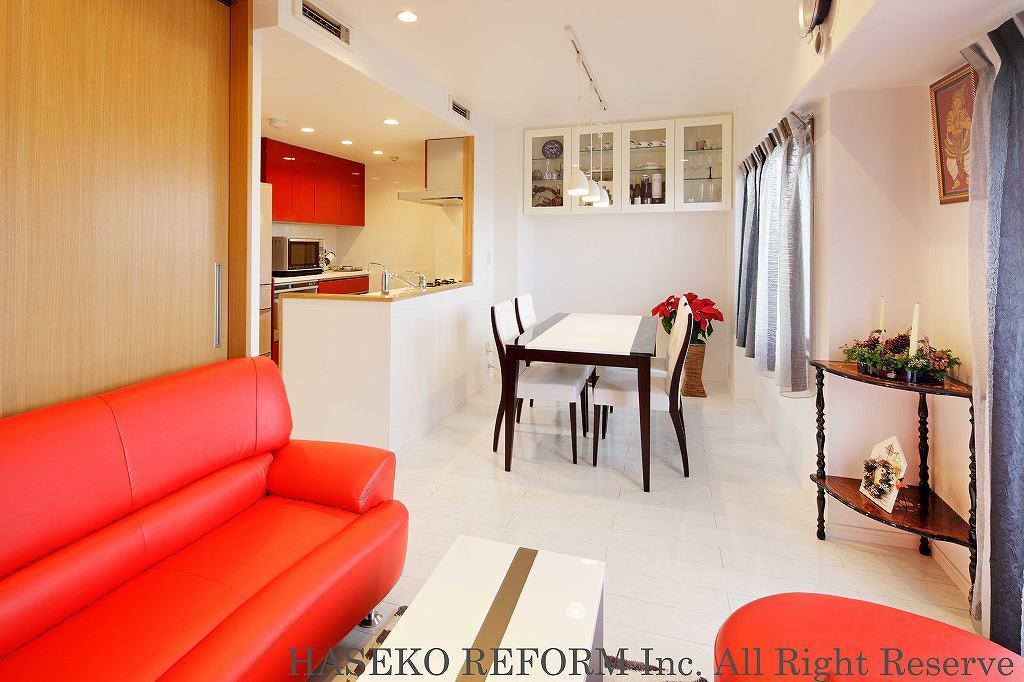白い石目調フローリング・白い壁のリビングにアクセントを効かせるのは、真っ赤なソファとこげ茶の家具。壁付けのコレクションボードはソファに座っても見える高さに。