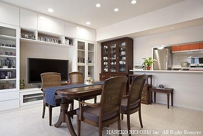 オープンキッチンで白色を基調としたリビングダイニング。テレビ側の壁は、真っ白の全面壁面収納に。