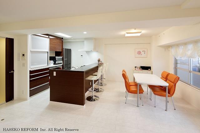 対面式オープンにしたキッチン。白色のフローロングをベースに、キッチンや建具のダークブランがアクセントに。