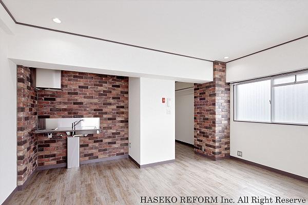ワンルームの賃貸マンション。ステンレス製のシンプルキッチンとレンガ調タイルのコントラストがアクセント。照明はダウンライトですっきり空間に。