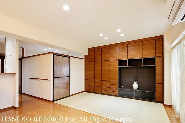 対面式キッチンから見渡せるリビングダイニング。大容量の壁面収納の前は畳コーナー。奥の寝室は上部壁をオープンにし、建具は民芸風のデザインで和モダンに。