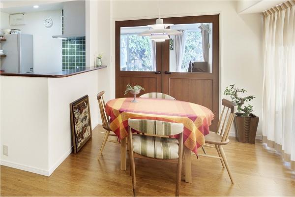 キッチンの吊り戸をなくし明るく開放的になったダイニングキッチン。ダイニング横のテラスドア風扉の上部はガラスとなっており、奥の洋室を通して、庭を楽しめます。