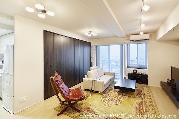 リビングに大きな壁面収納をつけて、すっきりとしたお部屋に。こだわりの照明と家具で落ち着きを感じさせる。