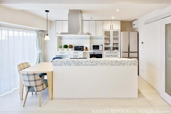 アイランド型キッチン。壁面は大容量の収納棚。キッチンカウンターと食器棚の水色モザイクタイルがアクセントに。